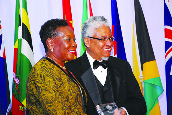 Delores Lawrence receives her award from UWI Vice Chancellor, Professor E. Nigel Harris. Photo by Heather Bubb-Clarke.