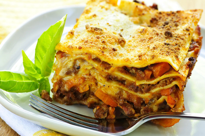Serving of fresh baked lasagna on a plate -- © Can Stock Photo Inc