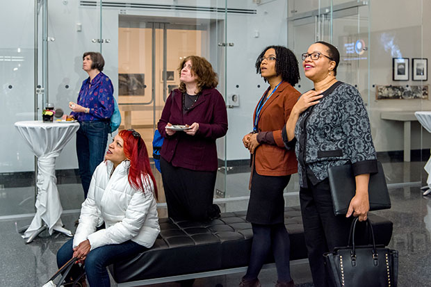 Dr. Denise O'Neil Green, Assistant Vice President/Vice Provost Equity, Diversity and Inclusion (EDI) at Ryerson University, at far right, with Mandissa Arlain, winner of the Viola Desmond Day -- Chloe Cooley Award -- beside her, joining others to watch a projection of the exhibition at the Ryerson Image Centre. Photo credit: Clifton Li.