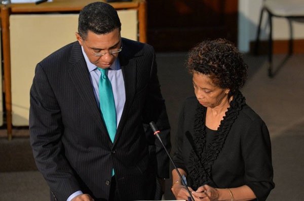 Prime Minister, the Most Hon. Andrew Holness, takes the Oath of Office during the swearing-in of Members of Parliament on March 10 at Gordon House. Clerk of the Houses of Parliament, Heather Cooke, observes the proceedings. Photo credit: JIS.