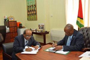Indian High Commissioner to Guyana, Venkatachalam Mahalingam, left, and Joseph Harmon sign MOU.