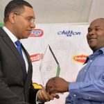 Prime Minister, Andrew Holness (left), presents Machine Operator at International Biscuits Limited (IBL), Ian Thompson, with an award of appreciation for his gallantry in risking his life to protect the assets of the company when he discovered a fire at facility. The presentation was made today (April 27), during the unveiling ceremony for new factory equipment at the IBL facility, in St. Andrew. Photo credit: Yhomo Hutchinson/JIS.