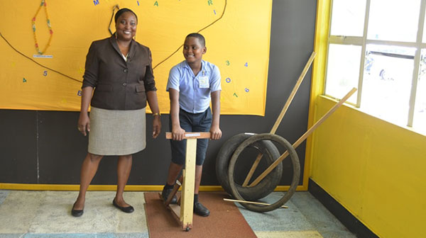 Administrator of the Guyana National Museum, Tamika Boatswain, shares in a child's enjoyment of a wooden scooter. Photo credit: GINA.