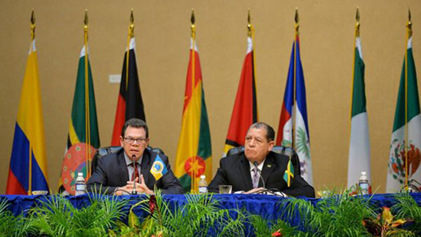 Jamaica Finance and Public Service Minister, Audley Shaw (right), listens as President of the Caribbean Development Bank (CDB), Dr. Warren Smith, addresses the closing press conference of the 46th annual meeting of the Board of Governors of the Caribbean Development Bank (CDB) on May 19 at the Montego Bay Convention Centre, in St. James. Photo credit: Yhomo Hutchinson/JIS.