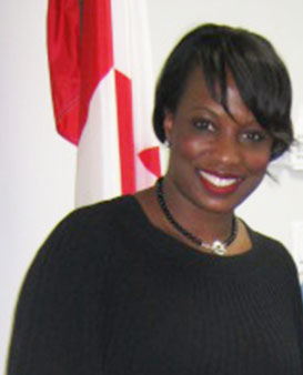 Caesar-Chevannes poses in front of the Canadian flag in her Whitby constituency office. Photo credit: Michael Van Cooten.