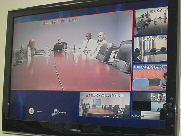 Video conference monitors show OECS officials in St Lucia (large monitor) and journalists from across the Caribbean.