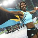 Bahamian Shaunae Miller, with her country's flag draped over her shoulders, celebrates her first place finish in the women's 400 metre final. Photo credit: CMC.