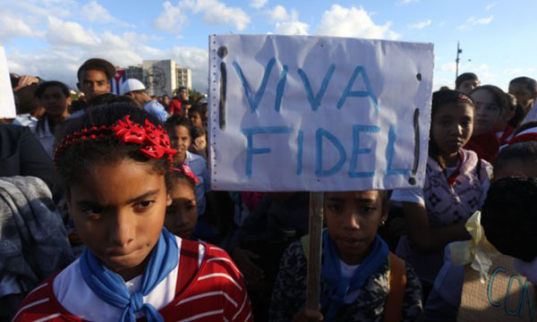 """Viva Fidel!"" reads a sign carried by a girl during a rally in the Plaza de la Revolución in Havana. Even after Fidel Castro withdrew from public life, his image has remained heavily present among every generation in Cuba, including the youngest. Photo credit: Jorge Luis Baños/IPS."