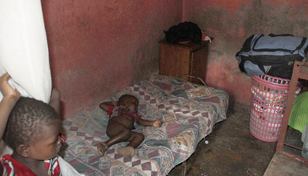 A two-year-old infant sleeps in a small room in Haiti, where she lives with her mother and three siblings. (CMC photo).