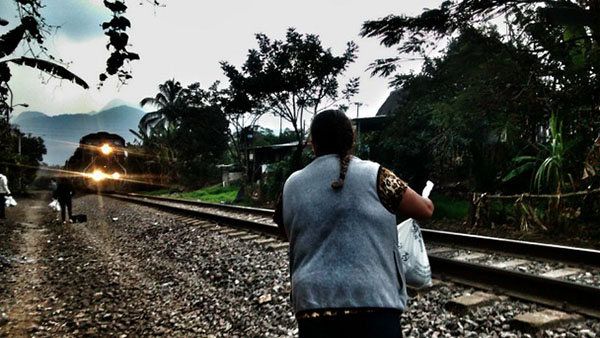 "A member of the migrant aid group ""Las Patronas"" waits for the train known as ""The Beast"", that was used by undocumented migrants to cross southern Mexico, to give them water and food. The Mexican government shut down the notorious train in August. Photo credit: Courtesy of the Mesoamerican Migrant Movement."