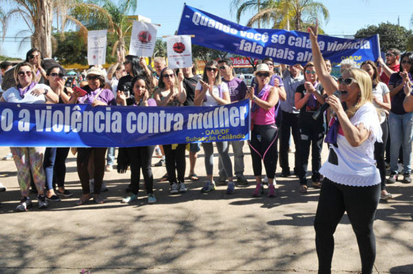 "Demonstrators call for full enforcement of the Maria da Penha Law against domestic violence in Brazil, 10 years after it was passed. One of the signs reads: ""When you remain silent, violence speaks louder."" Photo credit: Tony Winston/ Agência Brasília."