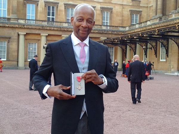Dr. Joe Daly displays his MBE award.