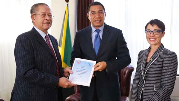 Former PM, Bruce Golding, left, presents the final report to Prime Minister, Andrew Holness, while Minister of Foreign Affairs and Foreign Trade, Kamina Johnson Smith, looks on. Photo credit: CMC.