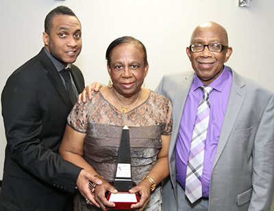 Darian Carrington, left, an insurance broker who sponsored the Matilda Van Cooten Award for Excellence in Parenting, presents it to Rev. Mr. Royston and Mrs. Claire Jones. Photo credit: Bruce Ramsay.