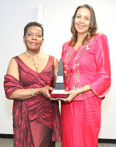 Marie Clarke Walker, right, receives the Excellence in Business award from its sponsor, NHI's CEO, Delores Lawrence. Photo credit: Bruce Ramsay.