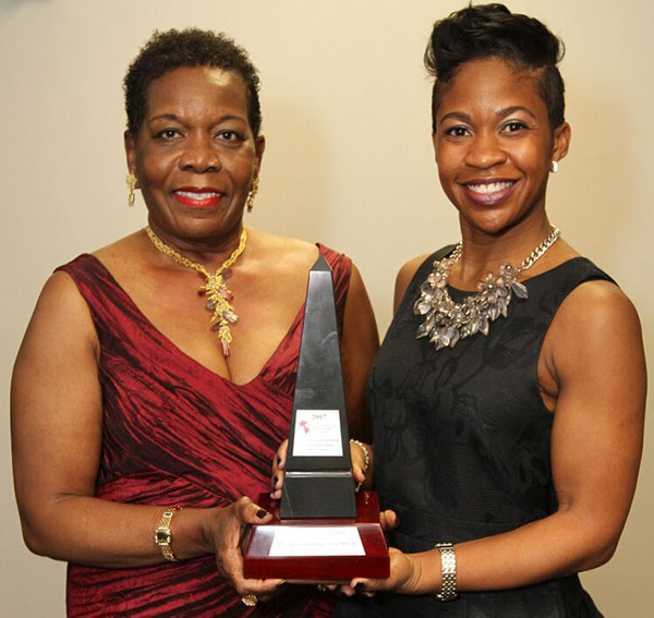 "Delores Lawrence, CEO of NHI, accepts her Lifetime Achievement Award from Mrs. Tricia Banfield, daughter of Joe Halstead, who sponsored the award. Lawrence was also surprised by the presentation of a customised walnut plaque that featured her image, adjacent to a poem, entitled ""A Lifetime Of Achievement"", written, in two days, by one of her friends, Lorna King. Photo credit: Bruce Ramsay."