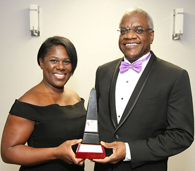 Dr. Sheridan Cyrus, right, a dental surgeon and owner of Sheridan Cyrus Professional Corp., hands over the coveted Excellence in Medicine award to its recipient, Sheryl Bernard, RN. Photo credit: Bruce Ramsay.