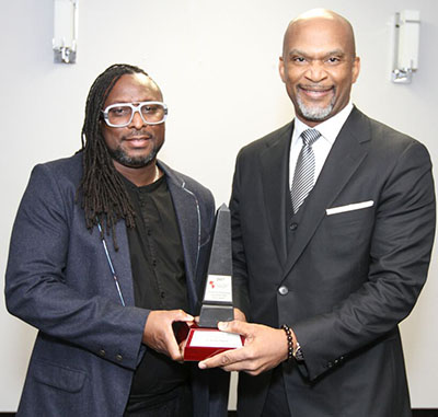 Dr. Rinaldo Walcott, left, accepts his award from dental surgeon, Dr. Lancelot Brown, who sponsored it. Photo credit: Bruce Ramsay.