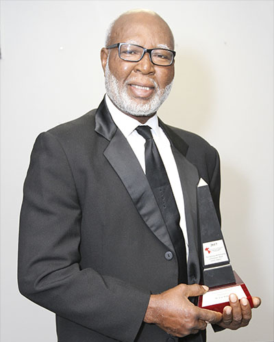 Eric Williams smiles in satisfaction as he displays his Excellence in Politics award. Photo credit: Bruce Ramsay.