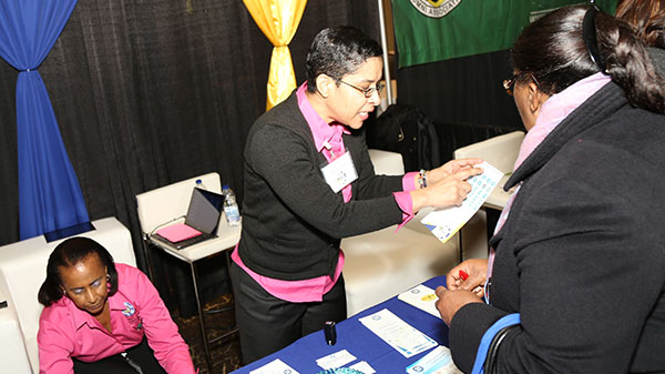 Cheriese Walcott, Registrar of Titles at the National Land Agency, speaks with a patron at the NLA's booth at the JN Group Expo held at the Pearson Convention Centre in Brampton, Canada on the weekend.