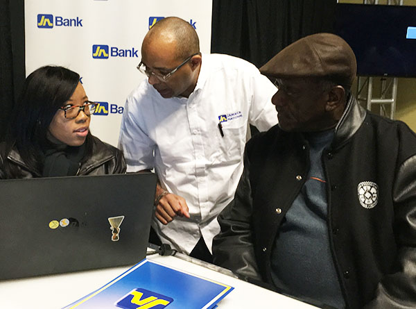 Harrington Stephenson, centre, of the JN Canada Representative Office, busy at the Jamaica National Group Expo, held at Pearson Convention Centre in Brampton on March 25. Photo by Neil Armstrong.