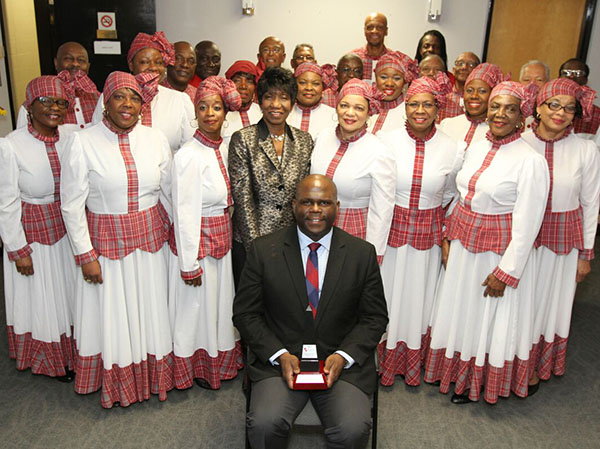 Jerrold Johnson, seated, Chief Representative Officer at Jamaica National Canada Representative Office, which sponsored the Excellence in the Arts and Entertainment award, after presenting it to Grace Carter-Henry Lyons (directly behind Johnson) the Artistic Director of  The heritage Singers, the recipient, posed with the group for this photo. Photo credit: Bruce Ramsay.