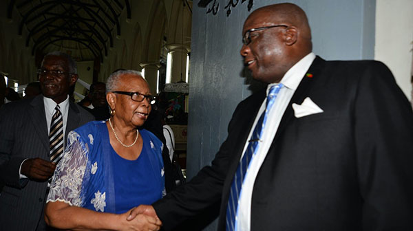 St. Kitts-Nevis PM, Dr. Timothy Harris (right) greets Lady Rosamund Inniss, at church, in a recent photo. Sir Probyn Inniss is in the background. Photo contributed.