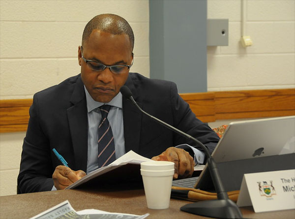In deep thought: Justice Tulloch jots down some notes before addressing the public consultation meeting in Kitchener, Ontario. Photo contributed.