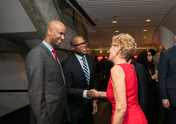 Mark Beckles, Head of RBC Insurance Advice Centre, and the 2017 ACAA recipient for excellence in management and leadership, shakes hands with Premier Wynne, while federal Immigration Minister, Ahmed Hussen, looks on. Photo credit: Office of the Premier.