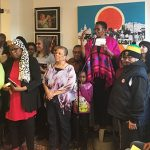 Itah Sadu (elevated and speaking at microphone), who recently traded in her signature dreadlocks for a short-cropped hairstyle, addresses the audience at the launch, last month, of her bookstore's new, larger location. Miguel San Vicente, Sadu's husband and together with whom she owns A Different Booklist, stands to her right in the photo. Photo by Neil Armstrong.