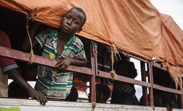 A young South Sudanese refugee looks out of a truck before being transported to the Imvepi settlement at the Imvepi Reception Centre, Arua District, in northern Uganda. Photo credit: UNHCR/David Azia.