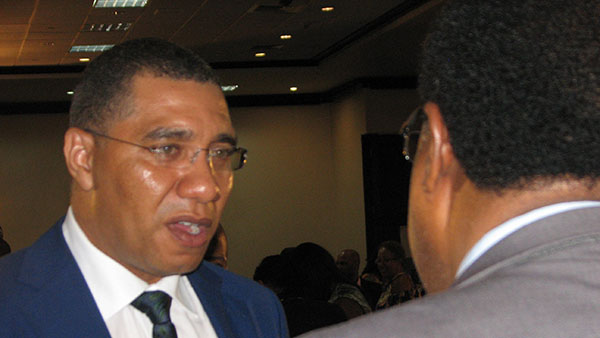 Prime Minister Andrew Holness engages a member of the audience in conversation. Photo by Michael Van Cooten.