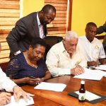 Minister of Transport and Mining, Mike Henry (3rd left), affixes his signature to a Memorandum of Understanding (MOU) for the growing of medicinal plants on mined-out bauxite lands. The agreement between the Jamaica Bauxite Institute (JBI) and Timeless Herbal Care was signed on Tuesday (September 5), at the Transport Ministry's Maxfield Avenue offices in Kingston. Others in the photo are (from left): Executive Director of the Jamaica Bauxite Institute (JBI), Parris Lyew-Ayee; Minister of Culture, Gender, Entertainment and Sport, Olivia Grange; Director, Public Relations and Corporate Communications, Transport and Mining Ministry, Vando Palmer; Chief Executive Officer of Timeless Herbal Care, Courtney Betty; and Chairman of the JBI, Bindley Sangster. Photo credit: Michael Sloley/JIS.