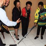 Olivia Grange, Jamaica's Minister of Culture, Gender, Entertainment and Sport prepares to poke the puck away from Greame Townsend, National Hockey Coach (2nd left) as it is being released by Donovan Tait, hockey player and coach (left). Looking on in anticipation are: Dorothy McLeod, Director, California Cultural Alliance (3rd left); founding members of the Jamaica Olympic Ice Hockey Federation -- Judith Smith (4th left) and Lester Griffin (right). The Jamaica Olympic Ice Hockey Federation and representatives from Tropical Ice Ventures of Canada paid a Courtesy Call on the Minister on December 1, at her offices in Kingston. Photo credit: JIS.