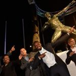 Prime Minister, Andrew Holness (centre), and retired track star, Usain Bolt (second right), lead in showing off the athlete's trademark 'To the World,' pose, at the unveiling of the eight-foot statue in Bolt's likeness at the National Stadium in St. Andrew on December 3. Others (from left) are Bolt's long-time coach and mentor, Glen Mills; Minister of Culture, Gender, Entertainment, and Sport, Olivia Grange; and sculptor, Basil Watson. Photo credit: Donald De La Haye.