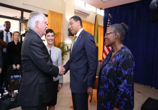 Prime Minister Andrew Holness (right) greets US Secretary of State, Rex Tillerson, and watched by a smiling Foreign Minister, Kamina Johnson-Smith (center).