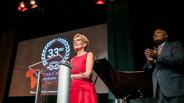 Ontario Premier Kathleen Wynne addresses the audience at the ACAA gala, last year, while Michael Coteau, Minister of Children and Youth Services and the Minister Responsible for the Anti-Racism Directorate, looks on. Photo credit: Office of the Premier.