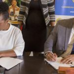 Executive Director of the Caribbean Export Development Agency, Pamela Coke Hamilton, left, and Daniel Best, Director of Projects at the Caribbean Development Bank, sign the agreement on behalf of their organisations.