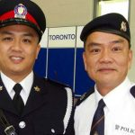 Toronto police officer, Ken Lam (left) poses with his father, David Lam, a n auxiliary police officer in Hong Kong. Photo courtesy of David Lam/Omni TV.