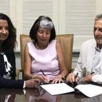 Naz Farrow, left, CEO of Colonial Group International Ltd.; Patricia Bryan, director and shareholder of Beacon Insurance Company Ltd.; and Gerald Hadeed, right, CEO and shareholder of Beacon Insurance Company Ltd. sign the partnership agreement between the two companies.