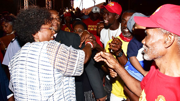 An elated Mottley (left) greets cheerful supporters after her resounding victory in last Thursday's blow out Barbados election.