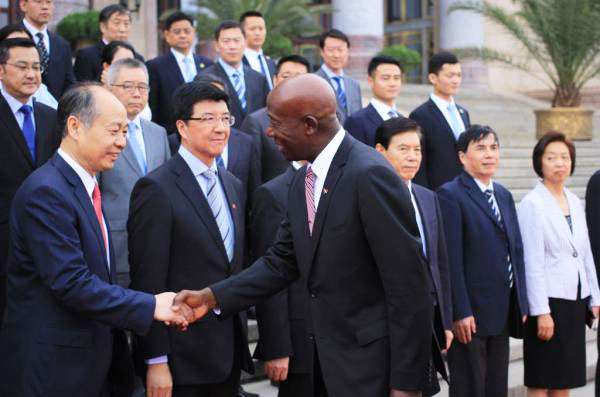 Prime Minister Rowley greets Chinese officials on his arrival in China.