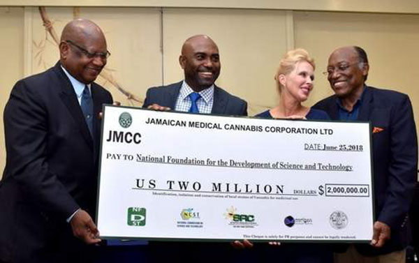 Dr. Andrew Wheatley (second left); Diane Scott (second right) CEO of JMCC Limited; Dr. Conrad Douglas (left) Director NFDST; and Professor Errol Morrision (right) Director General of the NCST, display a replica of cheque, representing the investment of US$2million in research and development, over the next 10 years. Photo credit: JIS.