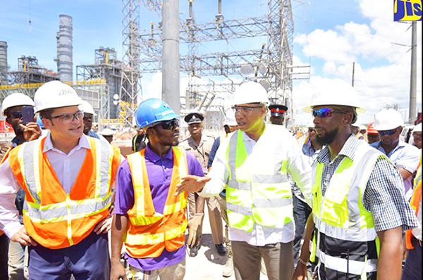 Prime Minister, Andrew Holness (second from right -- forefront), in discussion with workers on the construction site of the new US$330 million Jamaica Public Service (JPS) 190 megawatt (MW) power plant being built in Old Harbour Bay, St. Catherine. The workers are (from second left): steel fixer, Kennado Foster; and Works Manager, Jerome Williams. Also pictured is JPS President and Chief Executive Officer, Emanuel DaRosa (left). Photo credit: Yhomo Hutchinson/JIS.