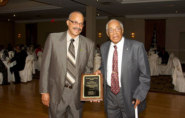 Dr. Bromley Armstrong presents an award, named for himself, to one of his protégés, Herman Steward, a union organiser and former President of the JCA.