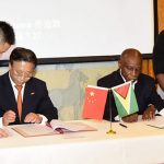 Guyana's Foreign Affairs Minister, Carl Greenidge (seated at right), and China's Ambassador to Guyana, Cui Jianchun, sign the Memorandum of Understanding (MOU), last Friday.