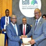 Guyana's Finance Minister, Winston Jordan (fourth from right), and IsDB Vice President of Sector Operations, Mansur Muhtar exchange a handshake after signing the agreement.