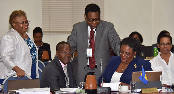 Prime Minister Mia Mottley in discussion with members of the Barbados delegation at the start of the Sixth Special Meeting of the Council for Finance and Planning at the Lloyd Erskine Sandiford Centre today. Photo credit: C.Pitt/BGIS.