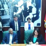 Siobhan Coady (seated, right), Minister of Natural Resources, Government of Newfoundland and Labrador, and Dominic Gaskin‎, Minister of Business, Cooperative Republic of Guyana, sign the MOU to further their respective oil and gas industries.