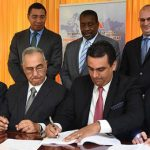 Prime Minister, Andrew Holness (left, standing); and Transport and Mining Minister, Robert Montague (2nd left, standing), observe as Chief Executive Officer of Mexican entity, Grupo Aeroportuario del Pacifico S.A.B. De C.V. (GAP), Raul Revuelta Musalem (2nd right, seated), signs the 25-year Norman Manley International Airport concession agreement on Wednesday (October 10). The signing took place at the Office of the Prime Minister. Also observing (from left, seated) are: President and Chief Executive Officer, Airports Authority of Jamaica (AAJ), Audley Deidrick; AAJ Chairman, Hon. William Shagoury; and Head of GAP subsidiary, PAC Kingston Airport Limited, Saul Villarreal Garcia. At right (standing) is NMIA Enterprise Team Chairman, Paul B. Scott. Photo credit: Michael Sloley.